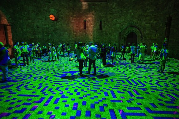 a kaleidoscope of colors  13th century castle courtyard lightened up with psychedelic lights Psychedelic lights modern artists green and blue